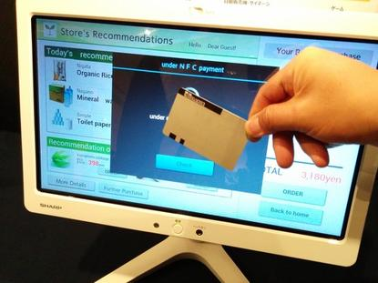 Sharp on Tuesday showed off a prototype screen embedded with a transparent NFC antenna that processes payment when touched with an NFC-equipped card. It could be used as a point of purchase in cash register or vending machine screens.