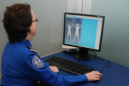 A security guard monitors results from the whole body scanner