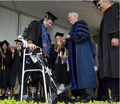 Graduating senior Austin Whitney, a paraplegic since 2007, walks toward Chancellor Robert Birgeneau (in blue) and Professor Homayoon Kazerooni at UC Berkeley's Commencement ceremony with the help of an exoskeleton. (Steve McConnell photo)