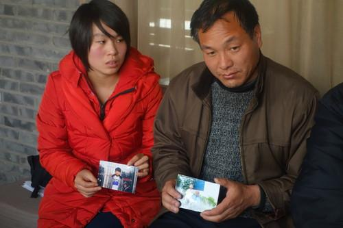 The father and cousin of deceased 15-year-old Pegatron worker Shi Zhaokun hold up his picture.