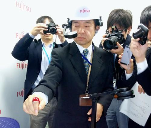 Fujitsu Laboratories shows off a gestural ring on Tuesday in Tokyo that lets users write numbers, Roman letters and Japanese characters in the air. It's aimed at maintenance and repair workers.