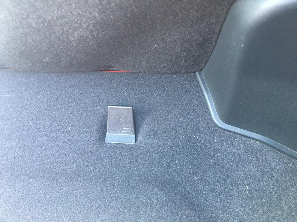 Looking in from the back window there are two plastic covers sticking out behind the rear seats.