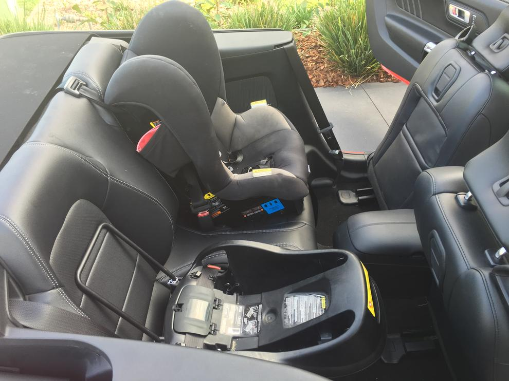 Both the car seat and toddler seat fit in the back. However, the capsule overhangs a lot meaning the front rear seat can't go back very far. The stiff, sculpted nature of the rear seats mean that you'll likely need towels to secure the capsule cradle.